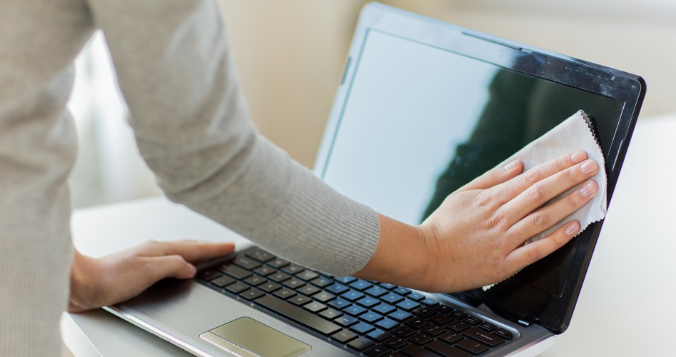 close up of woman hands cleaning laptop screen